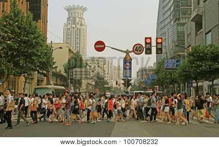 people are crossing road by crosswalk in Shanghai, China