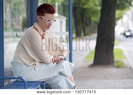 Woman Sitting At Bus Stop And Waiting