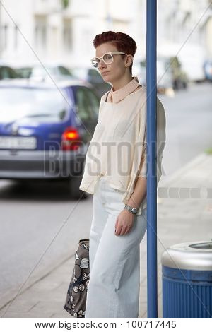 Woman Standing At Bus Stop And Waiting