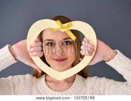 Closeup Portrait Of Young Female Holding Heart Shape Isolated