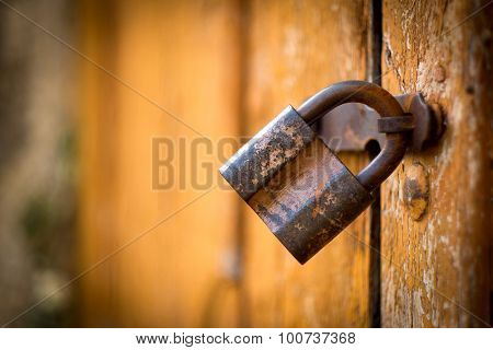Old rusty lock on the vintage wooden door