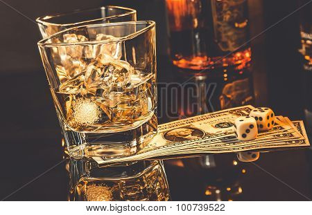 Glasses Of Whiskey Near Bottle On Dollars Money And Gaming Dice On A Black Table. Old Western Theme