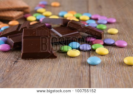 Chocolate Pieces With Color Smarties On Wooden Board