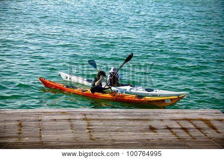 Orange And White Kayaks With Rowers Near Berth