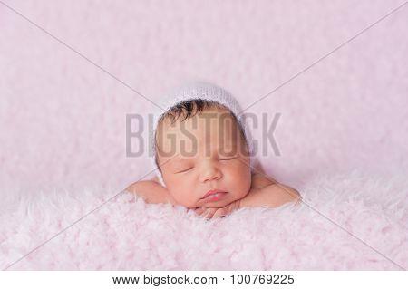 Newborn Baby Girl Wearing A Pink Knitted Bonnet