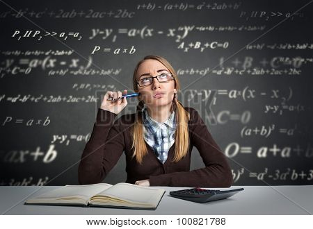 Young student with  thoughtful expression sitting at a desk with math formulas over her head