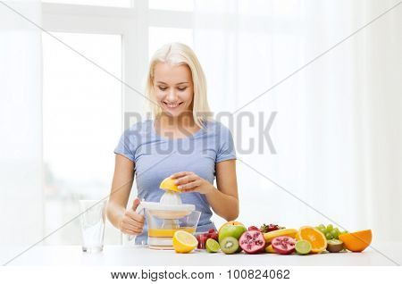 healthy eating, vegetarian food, dieting and people concept - smiling woman with squeezer squeezing fruit juice at home