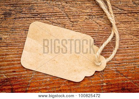 blank paper price tag with a twine against a rustic weathered wood poster