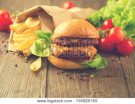 Fast food concept. Junk food over dark wooden table. Vintage style hamburger with fries and vegetables on rustic wooden table served with French Fries in crumpled brown paper. Homemade food