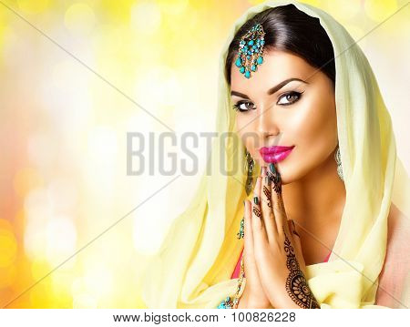 Beauty Indian woman  portrait. Hindu girl hold hands together is symbol prayer and gratitude. Indian model girl with black henna tattoos looking in camera. Mehndi. Indian marriage traditions