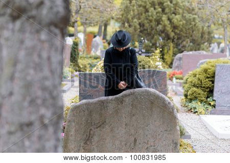 Woman In Mourning Praying At A Graveside