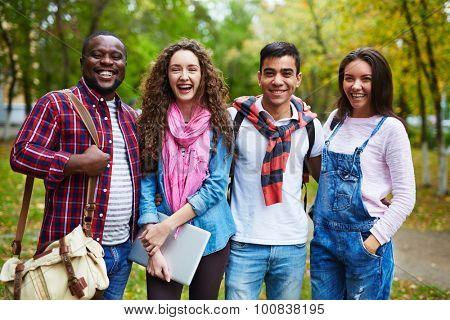 Joyful students in casualwear laughing outside