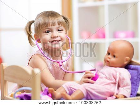 child playing doctor role game examinating her doll using stethoscope sitting in playroom at home, s