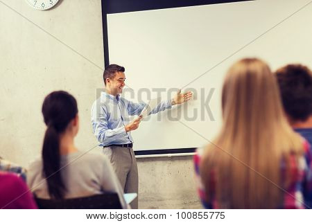 education, high school, technology and people concept - smiling teacher with notepad, laptop computer standing in front of students and showing something on white board in classroom poster