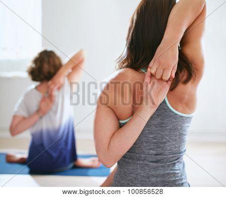 Women Practicing Gomukhasana In Yoga Class