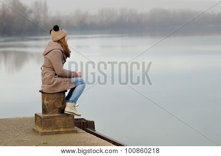 Lonely Sad Teenage Girl Sitting On The Dock On Cold Winter Day