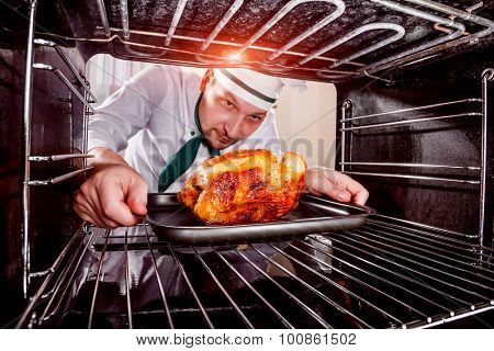 Chef prepares roast chicken (focus on chicken) in the oven, view from the inside of the oven. Cooking in the oven.Thanksgiving Day.