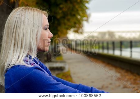 Beautiful Young Woman Sitting Outdoor On Cloudy Autumn Day