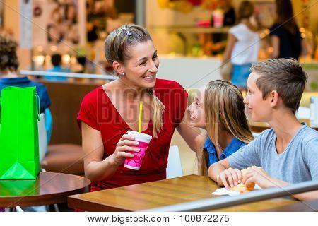 Family eating and drinking in cafe at shopping mall