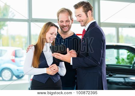 Seller or car salesman and clients or customers in car dealership presenting the interior decoration of new and used cars in the showroom on tablet computer
