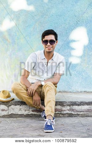 Young man travelling in latin america, sitting down in the street. Isla Mujeres, Mexico.