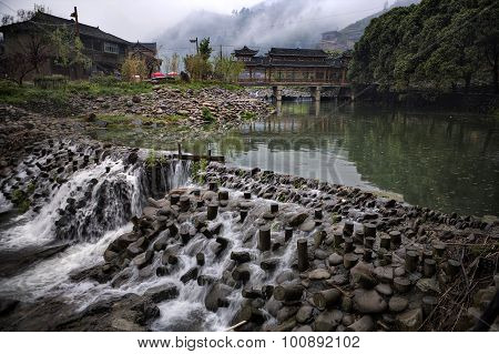 Dam On Rural River, Wooden Houses And Covered Carved Bridge