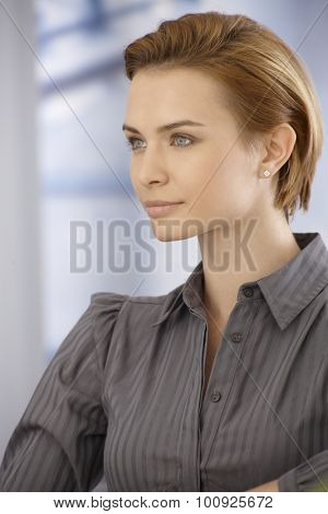 Portrait of young woman with short blonde hair looking away, half profile.