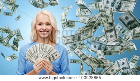 business, money, finance, people and banking concept - smiling businesswoman with dollar cash money over blue background