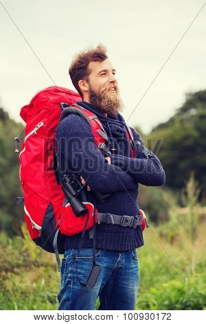adventure, travel, tourism, hike and people concept - smiling man with red backpack and binocular outdoors poster
