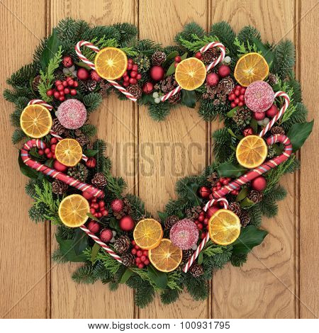 Christmas heart shaped wreath with dried fruit, candy canes, bauble decorations, holly, mistletoe and greenery over oak front door background. poster