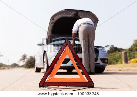 driver trying to figure out how to fix broken down car with red triangle to warn other road users