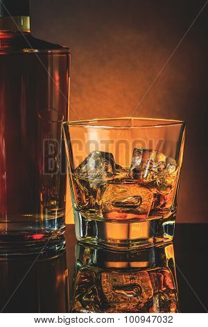 Glass Of Whiskey Near Bottle On Black Table With Reflection, Warm Atmosphere