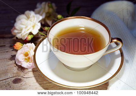 Tea In A White Porcelain Cup With A Gold Rim And Rose Decoration On Rustic Wood