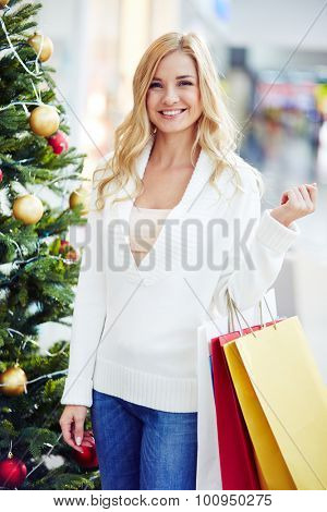 Happy female with paperbags looking at camera while standing by decorated firtree