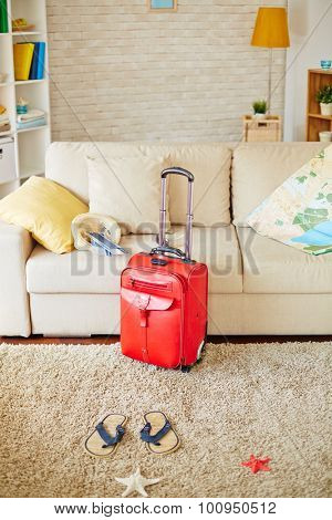 Sofa with map, pillow, hat and airline tickets and flipflops, sea star and suitcase near by