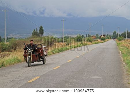 man is driving motor tricycle on the road nearly Lijiang