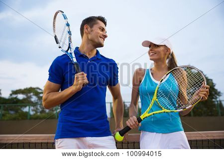 Couple of tennis players talking at the court after a match