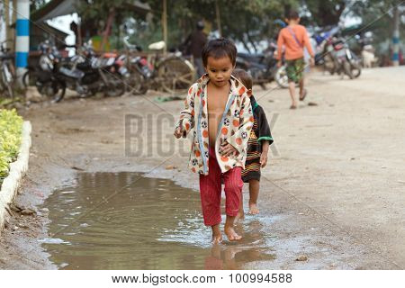 MANDALAY,MYANMAR,JANUARY 19, 2015 : A little boy is playing with his friend in the street, walking in a rain puddle in a slum area of Mandalay, Myanmar (Burma).