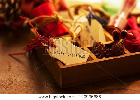 Preparation for Christmas. Wooden tray with ribbons, Christmas tags, on an old wooden table with vintage feel. Intentionally shot with warm incandescent type lighting and shallow depth of field.