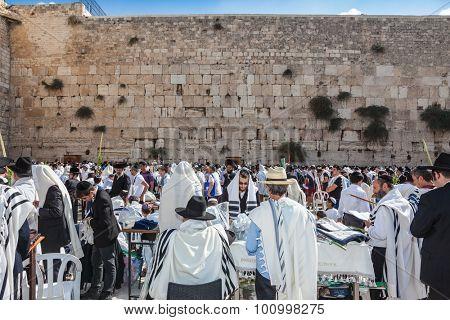 JERUSALEM, ISRAEL - OCTOBER 12, 2014:  Hhuge crowd of faithful Jews wearing white prayer shawls and black long-skirted coats. Morning autumn Sukkot