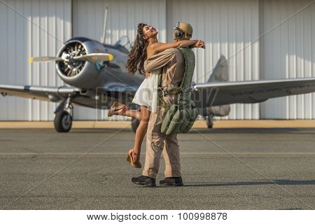 A brunette model in vintage clothing with a pilot and a WW II aircraft poster