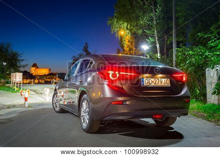 POLAND-AUGUST 9, 2015: New Mazda 3 captured at dusk with long exposure technique. Mazda 3 is a popular compact car manufactured in Japan by the Mazda Motor Corporation.
