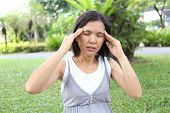 Thai pregnant mom have headache in the garden because of stressful. poster