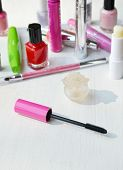 Pink mascara stick, eyeliner, lipstick, pencil and other cosmetics on the white dressing table poster