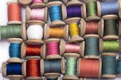 colored cotton thread for sewing on wooden spools on a white background, needlework poster