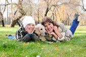 Mother and son together having fun in the autumn park playing with a golden retriever. poster