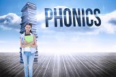 The word phonics and student holding notepads against stack of books against sky poster