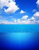Underwater scene and blue sky with white clouds. Water surface split by waterline poster