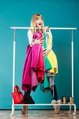 Funny happy woman girl taking grabbing all clothes coats and shirts in wardrobe. Young girl shopping in mall. Fashion clothing sale concept. poster