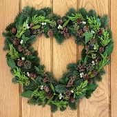 Winter and christmas heart shaped wreath with mistletoe and greenery over oak front door background. poster